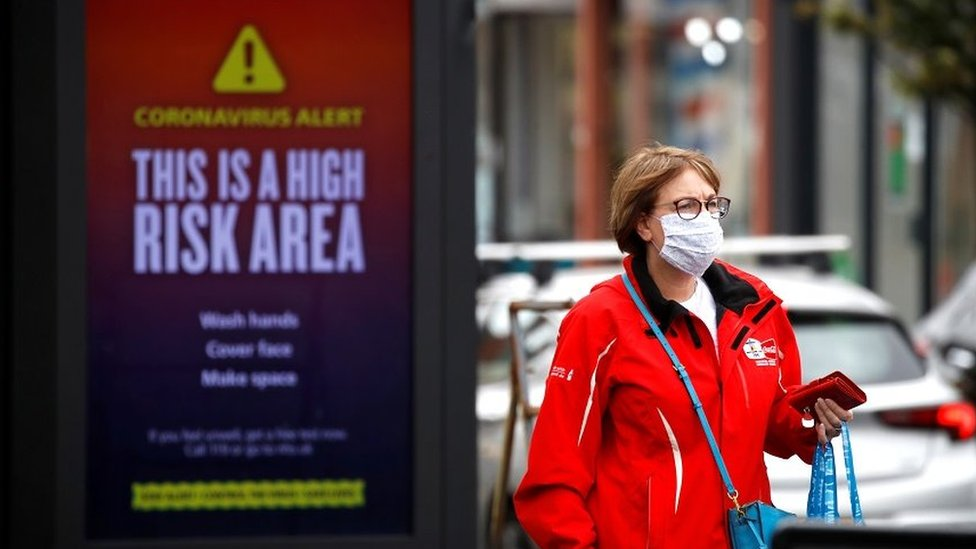 A woman wearing a protective mask walks past a warning sign
