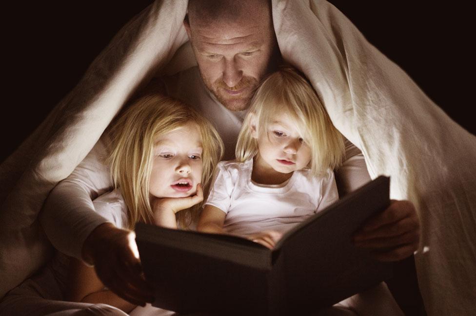 Un padre le lee a sus dos niñas