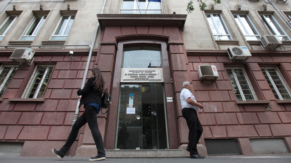 """People walk past Bulgaria""""s National Revenue Agency building in Sofia"""