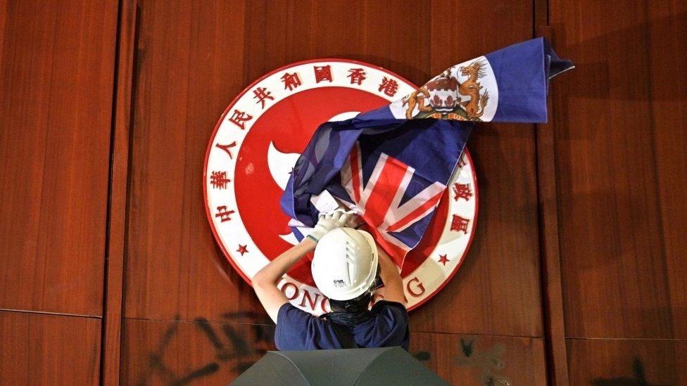 - A protester attempts to cover the Hong Kong emblem with a British colonial flag after they broke into the government headquarters in Hong Kong on July 1, 2019