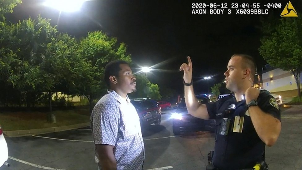 Garrett Rolfe conducts a field sobriety test on Rayshard Brooks in a Wendy's restaurant car park