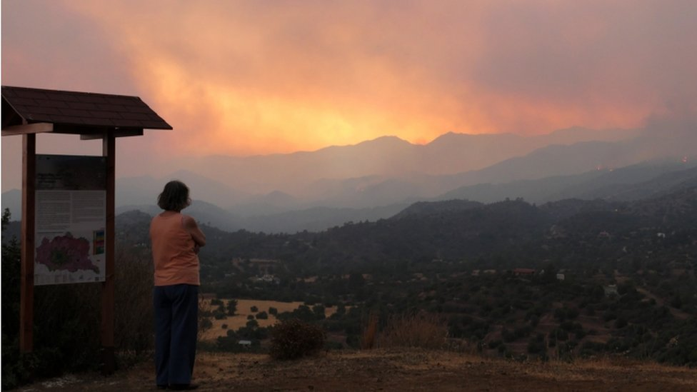A woman looks at the smoke and fire from the fire