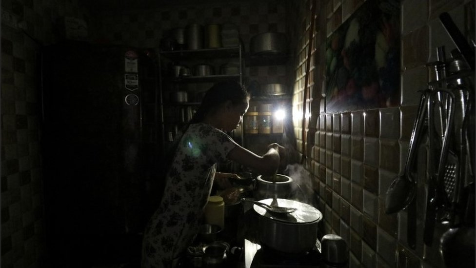 A woman uses her mobile phone torch as she cooks food inside her kitchen during a power outage in Mumbai, India, October 12, 2020.