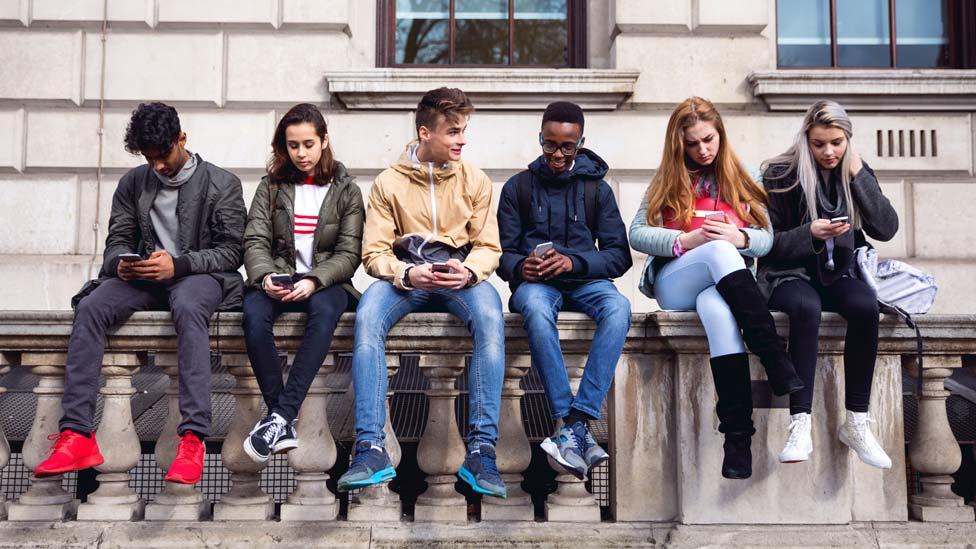 Teenagers looking at their phones (file photo)