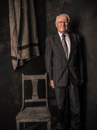 Foto de Eddie Jaku con una silla y manta como las que solía tener en Auschwitz