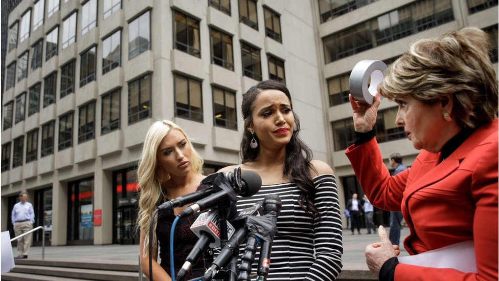 former Houston Texans cheerleaders Hannah Turnbow and Angelina Rose look on as attorney Gloria Allred holds up a roll of duct tape during a news conference