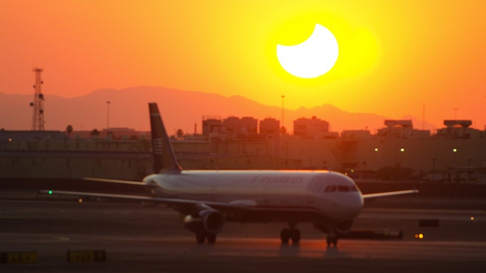 Plane taxis at Phoenix airport in front of sunset