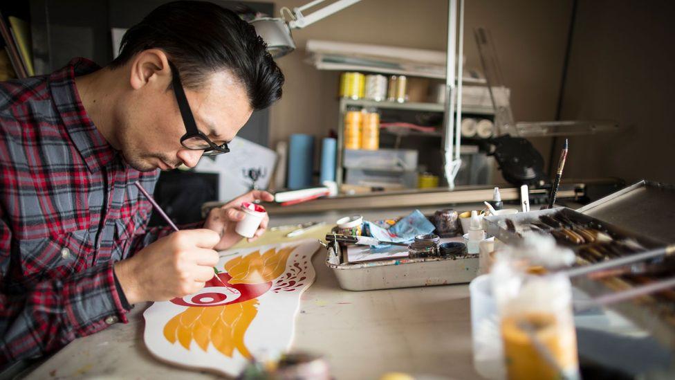 Un hombre con un proyecto personal pinta un cartel