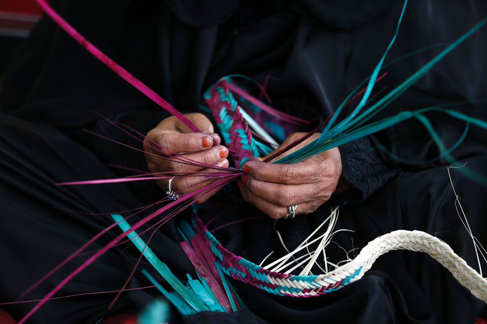 Emirati woman weaving palm fronds