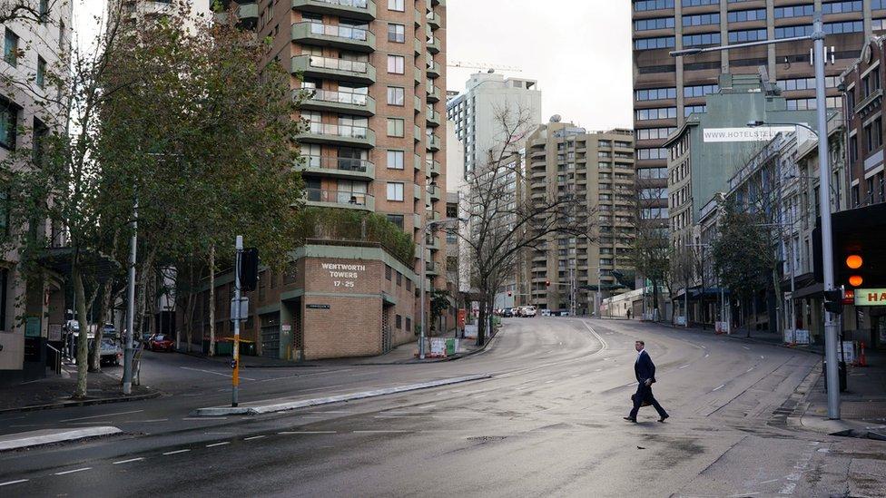 Um homem atravessa uma rua deserta no centro de Sydney durante lockdown