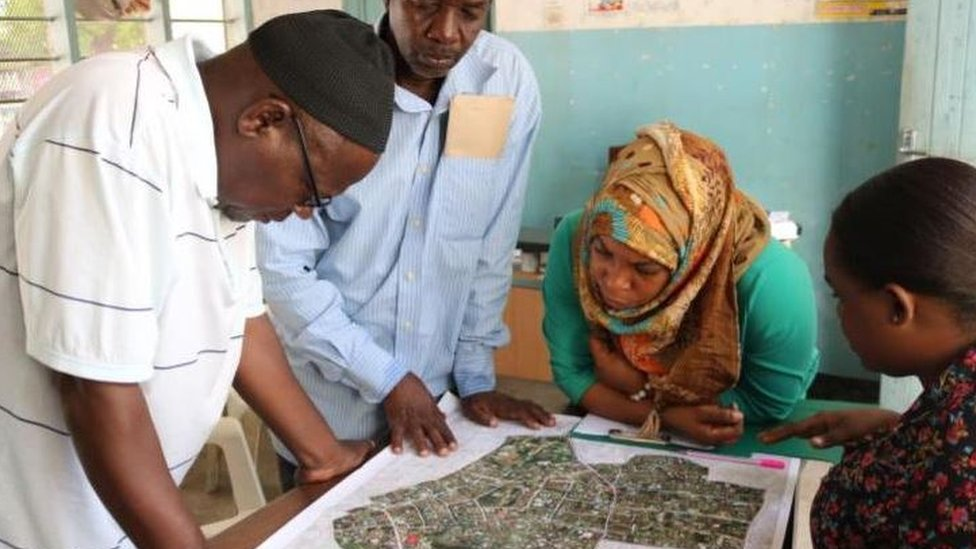A group of Tanzanians looking at the Open Source Map.