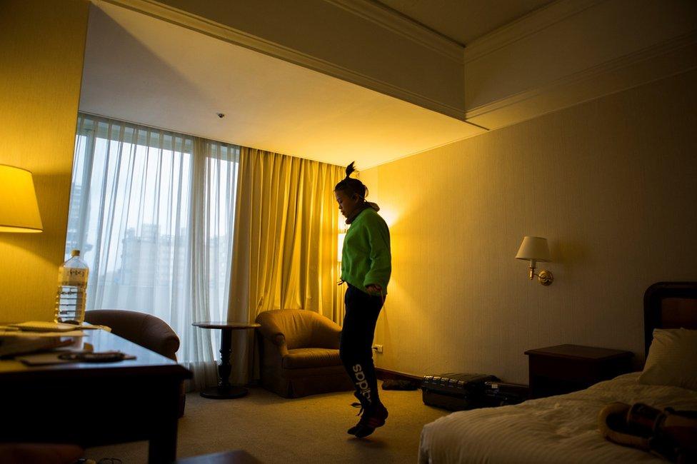 Huang vežba u hotelskoj sobi kako bi skinula višak kilograma.