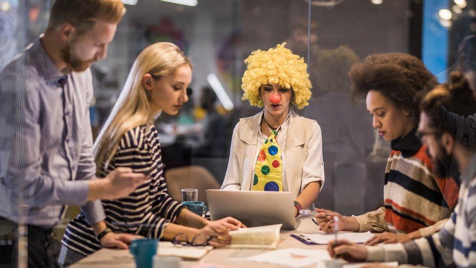 Una mujer con peluca y corbata de payaso en reunión de trabajo