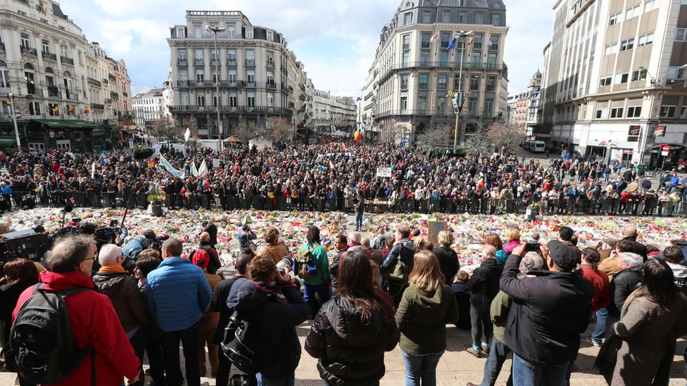 March goes past the makeshift memorial in the Stock Exchange Square, Brussels, on 17 April 2016