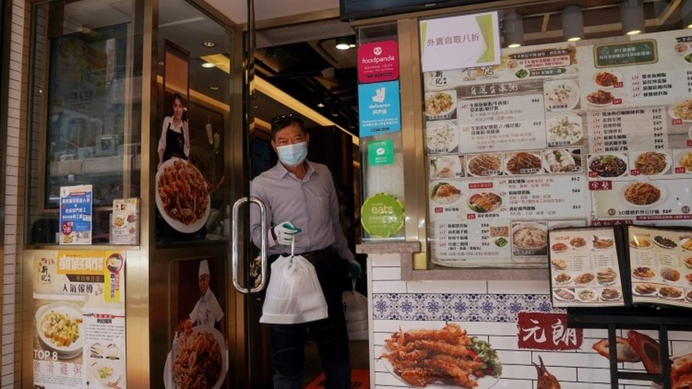 A man gets a takeaway from a Hong Kong restaurant