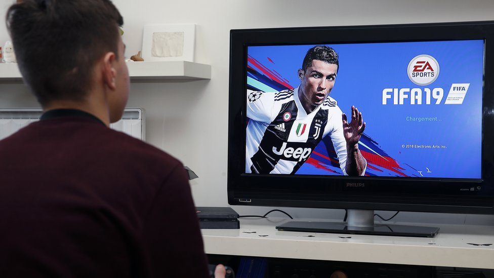 A man playing Fifa 19. We can see an image of Cristiano Ronaldo in a Juventus kit on the TV.