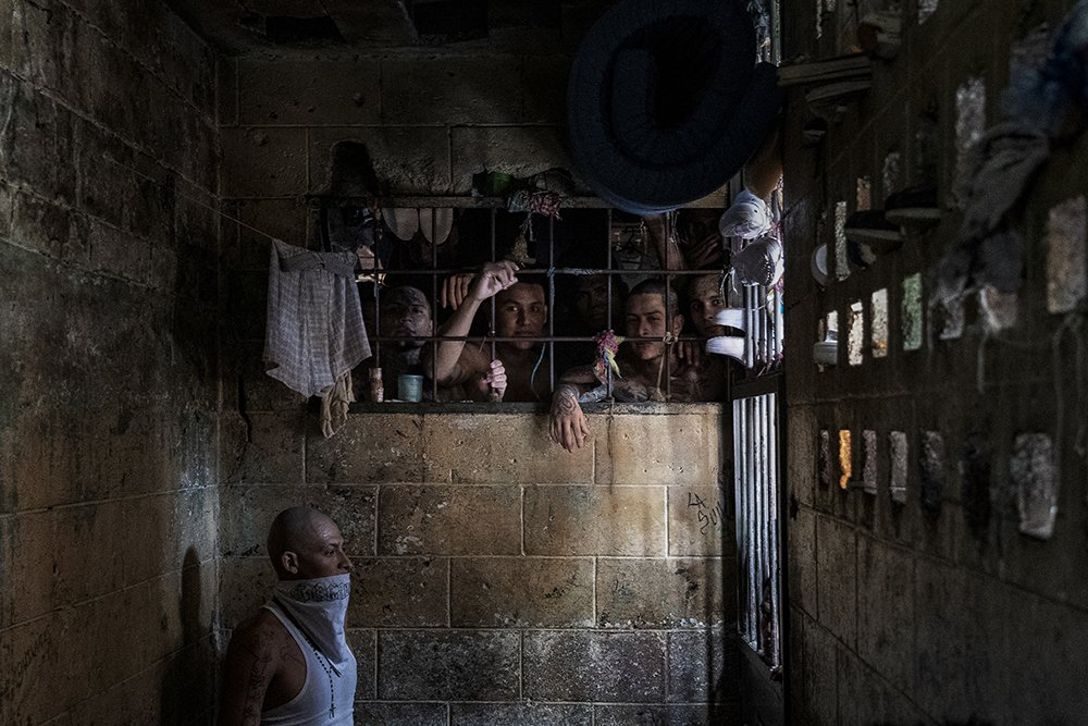 Inmates look out of an overcrowded cell, while a man wears a bandana across his face because of the putrid smell. Penal Center of Quezaltepeque, El Salvador. November 9, 2018.