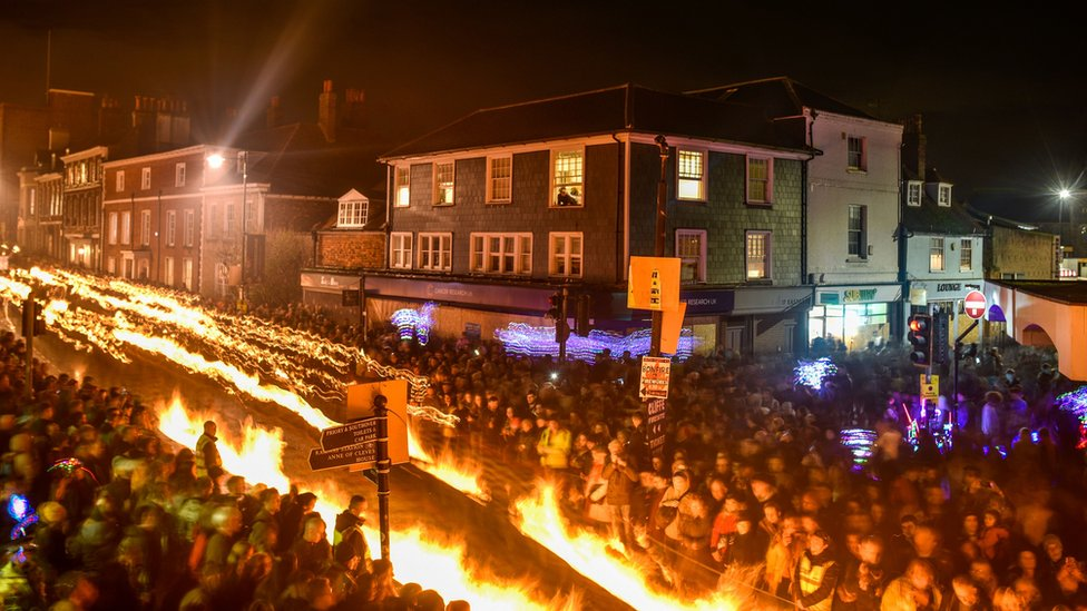 Those parading hold burning torches as they file through the streets