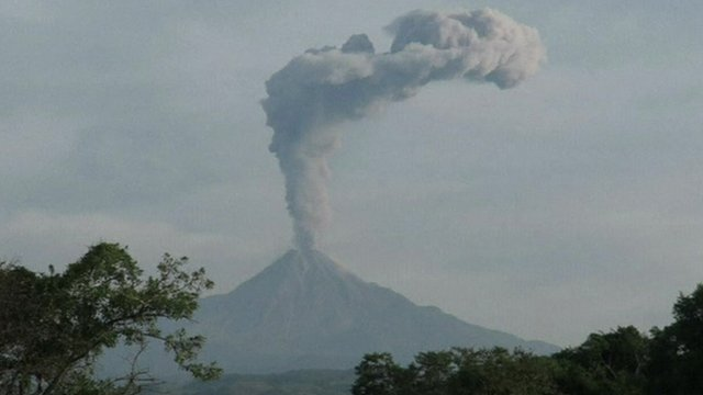 Erupting volcano sending a column of ash and vapour into the air