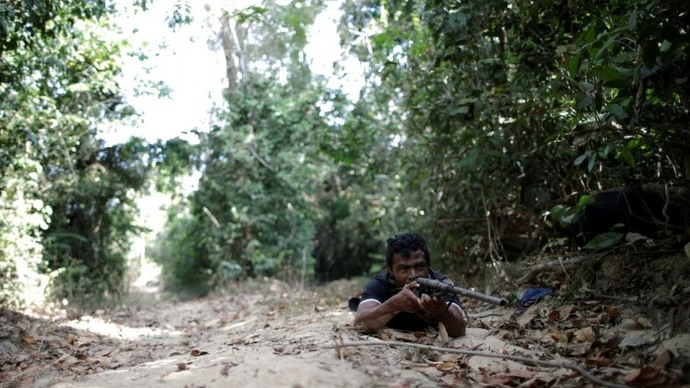 Paulo Paulino Guajajara holds a gun during the search for illegal loggers in September
