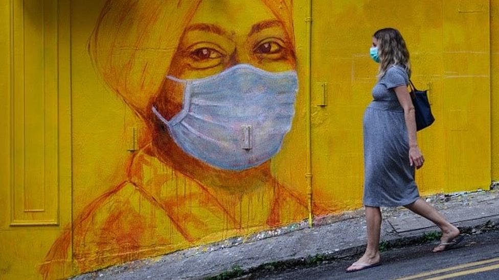 Gestante usando por máscara anda numa rua com um grafite de outra mulher, que também usa máscara