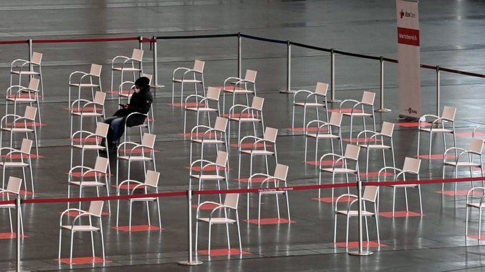 A person sits in the waiting area of a vaccination centre in Nuremberg, southern Germany