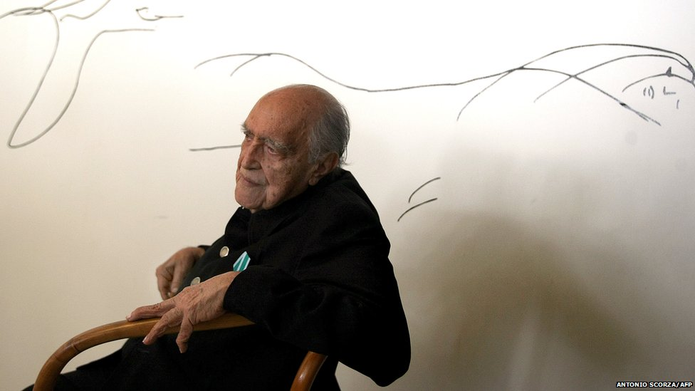 Brazilian architect Oscar Niemeyer poses at his studio in front of a drawing on 14 December 2007