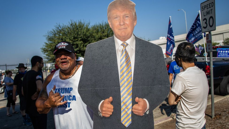 San Tee holds a President Donald Trump mannequin before a Pro-Trump car caravan in Long Beach, California on October 3, 2020
