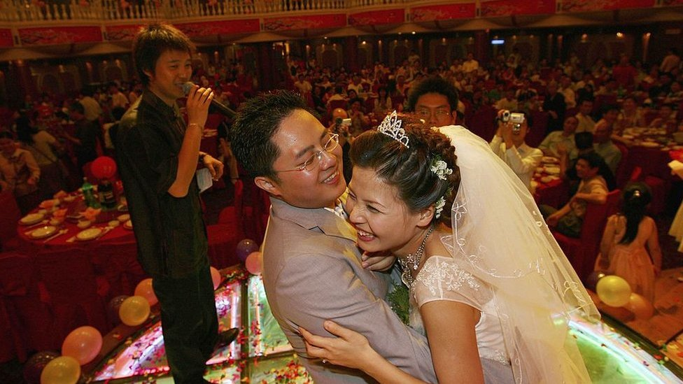 A couple hug during feast at a wedding ceremony on 6 May 2006 in Nanchang of Jiangxi Province, China.