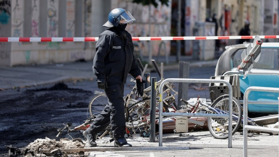 A police officer walks past extinguished barricades