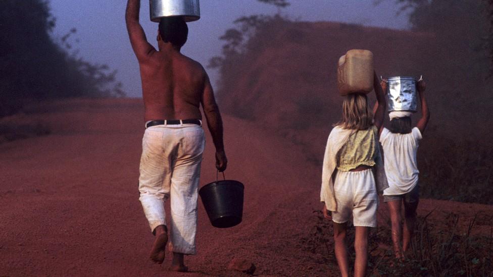 Una familia camina con recipientes de agua durante una sequía en el estado de Pará en Brasil