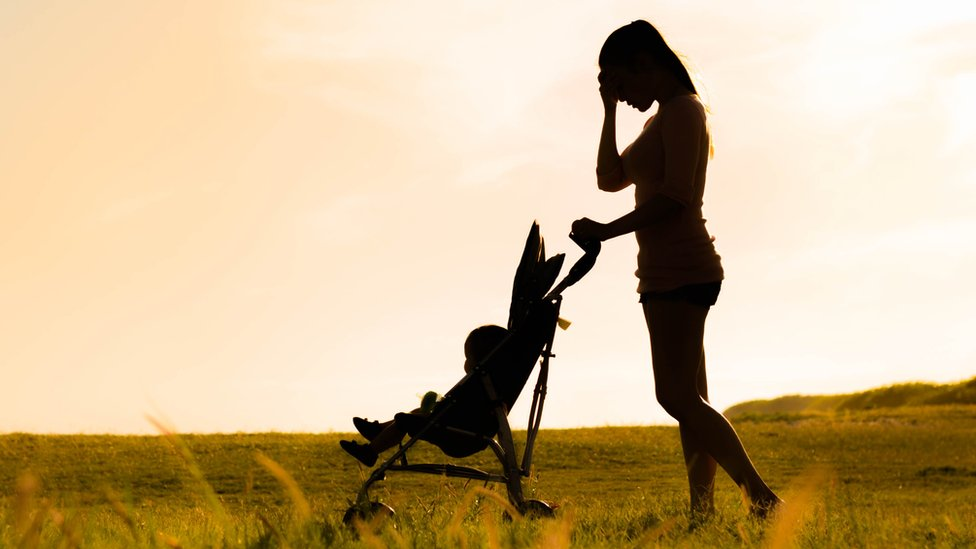 silhouette of woman with baby in pushchair with her head in her hands