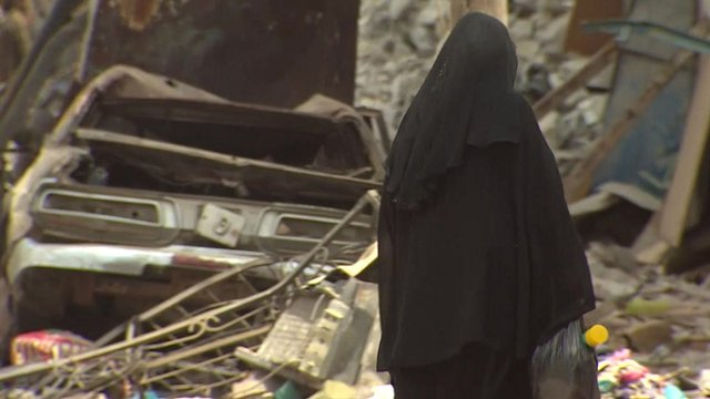 Woman walks among rubble in Aden