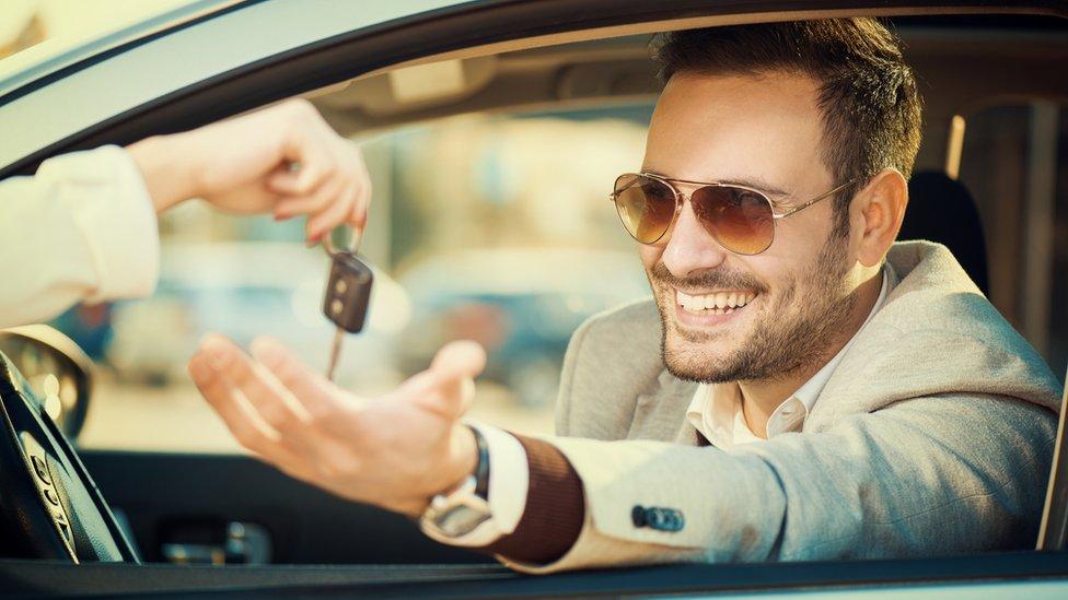 Hombre recibiendo llave de su nuevo carro