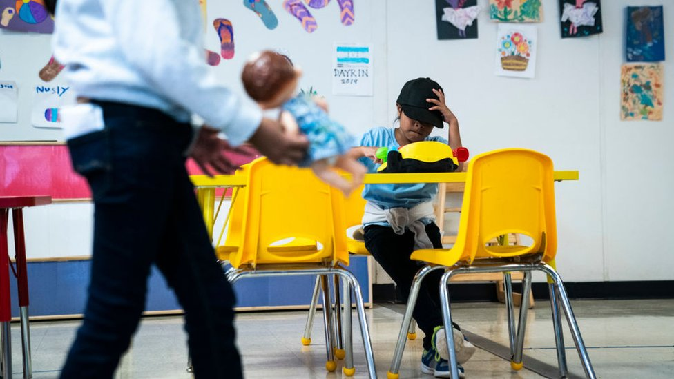 A girl is sitting in one of the classrooms at the South Texas Family Residential Center in 2019.