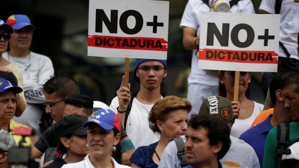 """Demonstrators holding signs that read """"No more dictatorship"""" take part in a protest against President Nicolas Maduro government, in Caracas, Venezuela, May 13, 2017"""