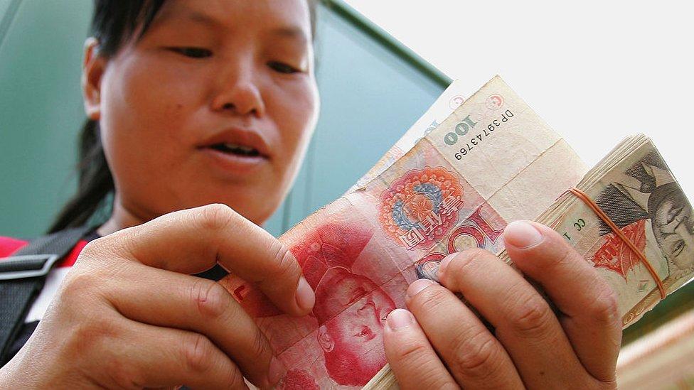 Mujer china con billetes de yuan.