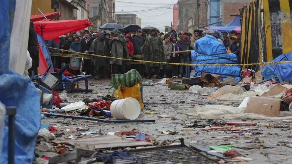 Locals watch from behind of a barricade at the scene of an explosion a day before, that caused six dead and 28 injured in a street market that remains cordoned off while the investigation continues in the city of Oruro, Bolivia,