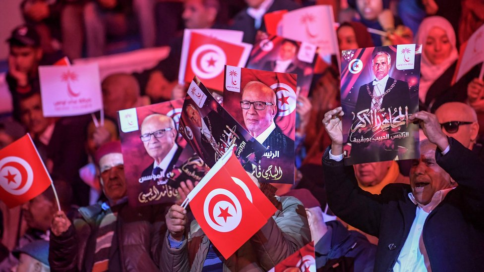 Supporters of President Essebsi wave photos of him and the country's founder at a meeting of the ruling party in Tunis, April 2019