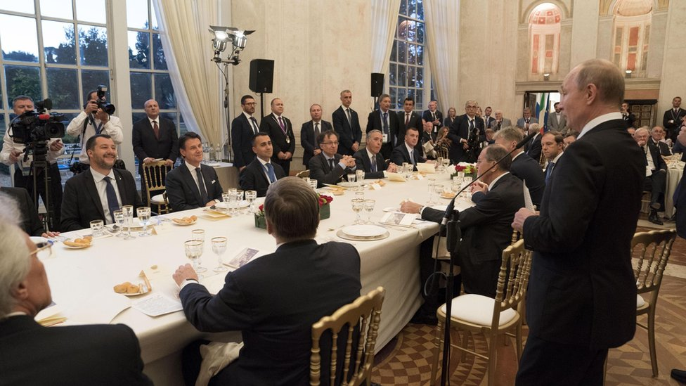 Vladimir Putin (standing) at a meeting with Italian officials in Rome, 4 July