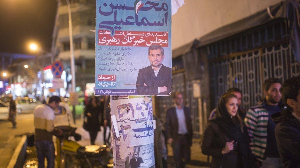 People walk past electoral posters in downtown Tehran, Iran