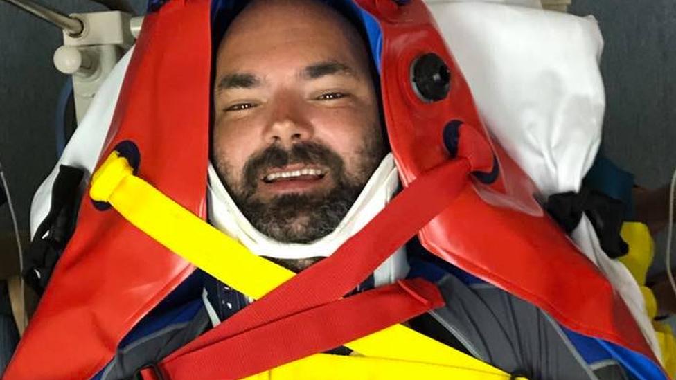 Tom Benson on a stretcher