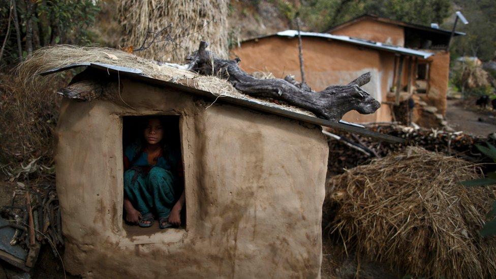 A girl sits inside a Chhaupadi shed