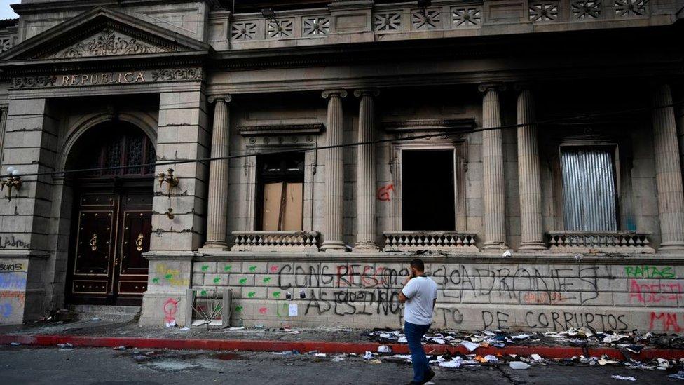 Fachada del Congreso de Guatemala con grafiti, ventanas rotas y ahumadas