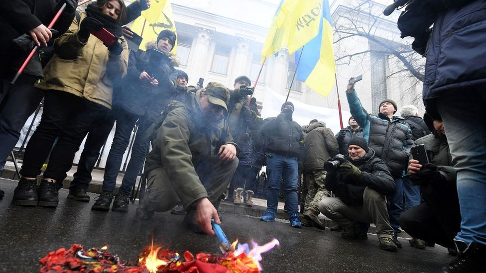 Activists burn the Russian flag and St George ribbons - symbols of the so called 'Russian world' - as they call for the deputies to recognise Russia as an aggressor state during a rally in front of the Ukrainian parliament in Kiev, on January 16, 2018