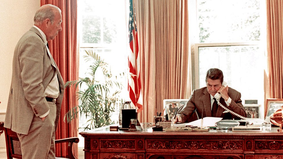 وزير الخارجية الأمريكي جورج شولتز يشاهد الرئيس الأمريكي رونالد ريغان يتحدث عبر الهاتف