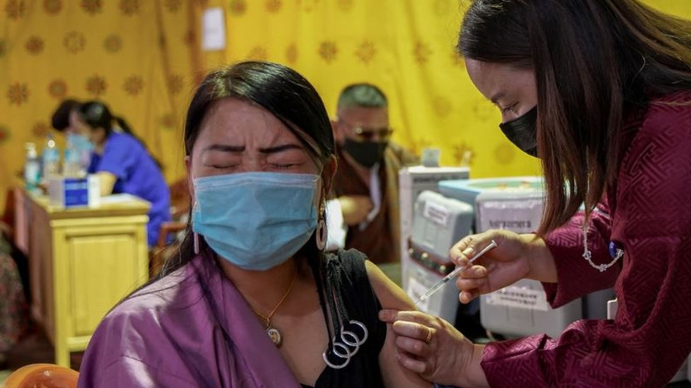 Um trabalhador de saúde vacina uma mulher em um centro temporário de vacinação em Thimpu, Butão, em 26 de julho