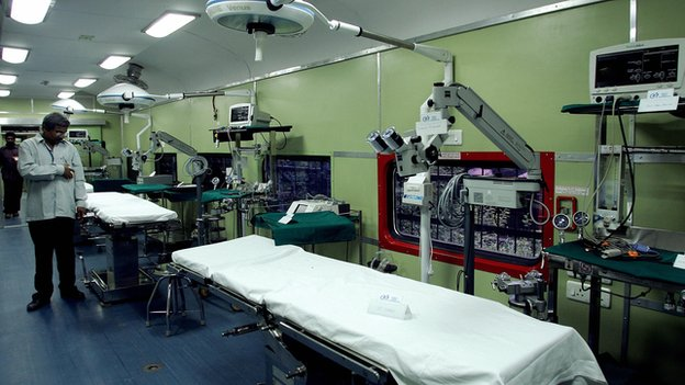 A doctor stands next to operating tables inside a train