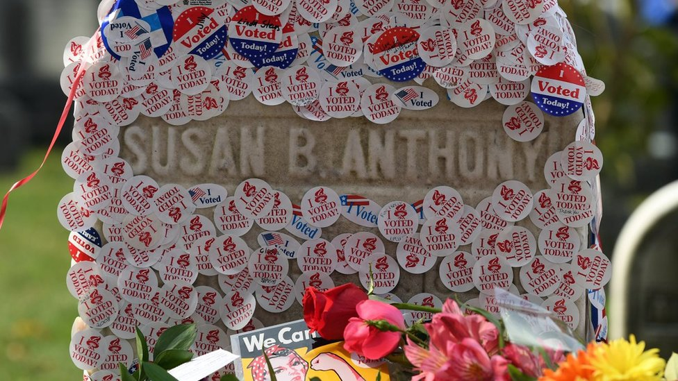 Susan B Anthony's grave is photographed littered with stickers