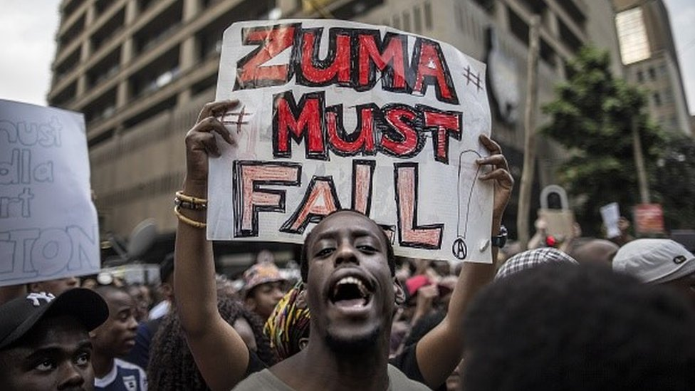 A student holds a placard reading 'A placard with 'Zuma must fall' outside the Luthuli House, the ANC headquarters, on October 22, 2015, in Johannesburg